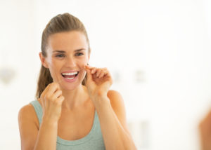 Young woman flossing teeth