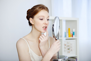 Woman looking at teeth in mirror