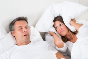 Woman closing her ears next to her husband sleeping