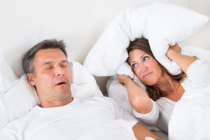 Woman annoyed by man's snoring