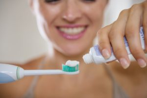 woman putting toothpaste on electric toothbrush
