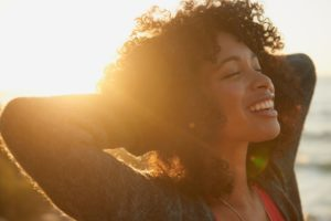 woman smiling in the sunset after seeing cosmetic dentist in Virginia Beach